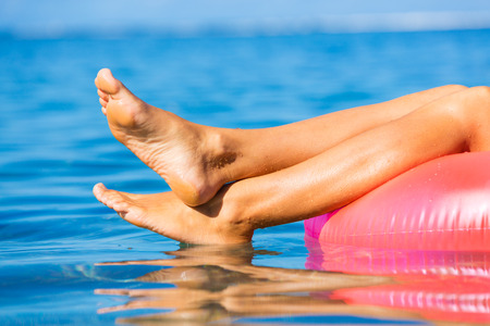 29967566 - beautiful sexy girl floating on raft in tropical ocean. close up view of feet. relaxation concept.